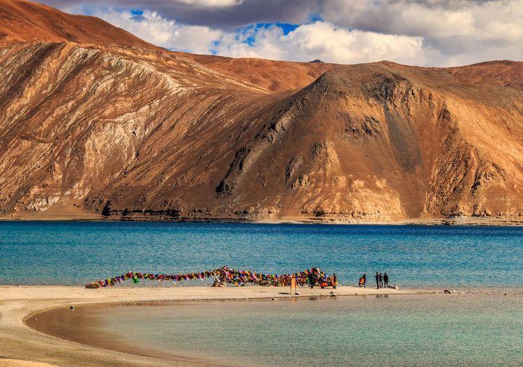 People on lake against mountain range