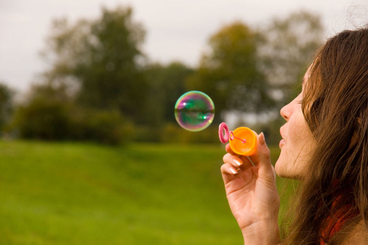 Cute girl blowing bubbles outdoors (close up) Wand Bubble Blowing Girl Happiness Joy Playful Cheerful Childhood Carefree Summer Soap Activity Outdoors Smiling Leisure Innocence Woman Grass Freedom Dreams Nature Imagination Spring Cute