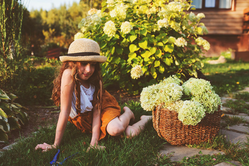 Girl sitting with flowers in basket at yard