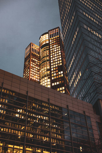 Low angle view of illuminated buildings against sky at dusk