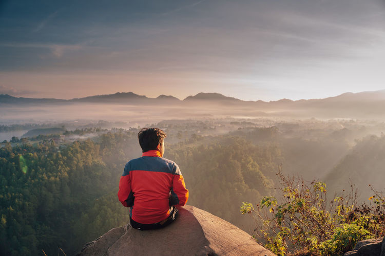 Rear view of man sitting on mountain against sky during sunset