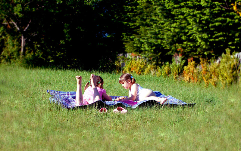 Children Natural Sister Adult Casual Clothing Childhood Day Field Friendship Full Length Grass Green Color Land Leisure Activity Nature Outdoors Picnic Playing Positive Emotion Real People Sitting Togetherness Tree Two People Unplugged