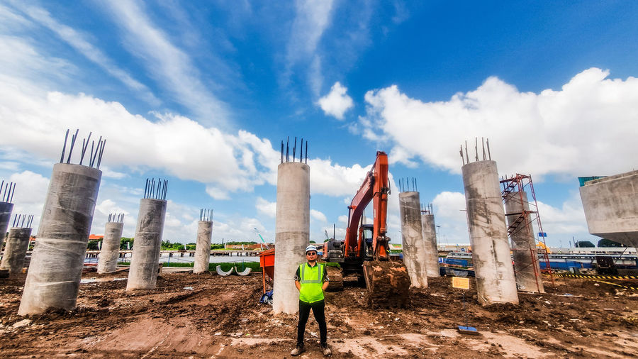 Man standing on construction site against sky