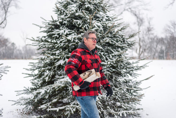 Full length of young man standing on tree during winter