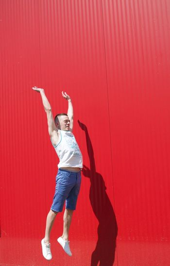 Full Length Of Man Jumping Against Red Wall