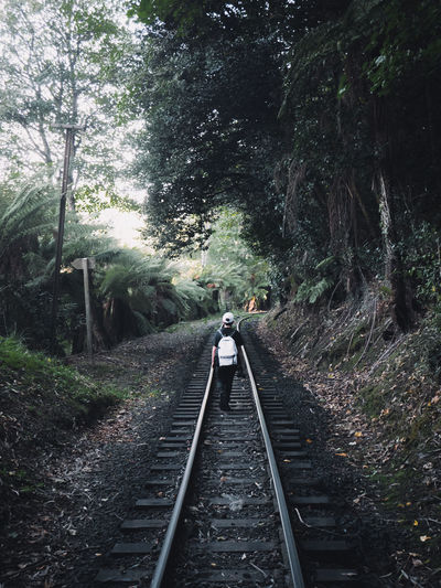 Rear view of person walking on railroad track
