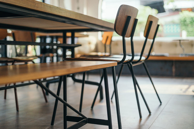 Close-up of empty chairs and table in cafe