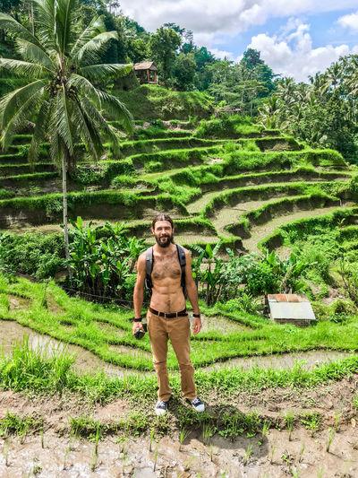 Full length of shirtless man standing on field