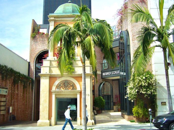 Citycape, Rodeo Drive 🌿🎉✨ Rodeo Drive Architecture Building Exterior Built Structure Plant Tree Real People Building Lifestyles Adult Standing Arch Outdoors Nature Entrance One Person Women Sunlight Day Architecture Palm Tree Tropical Climate Tree Entrance Full Length Street Rear View Nature Architecture City