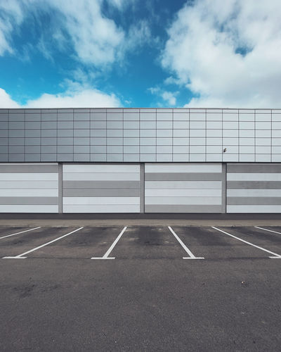 Wall of a building with an empty parking lot against a blue sky.