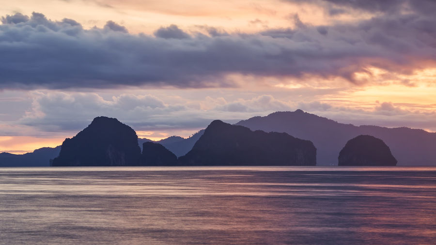 Scenic view of sea and silhouette mountains against sky at sunset
