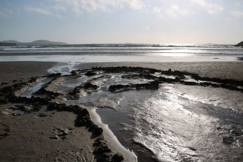 High Angle View Of Muddy Seascape Against Cloudy Sky