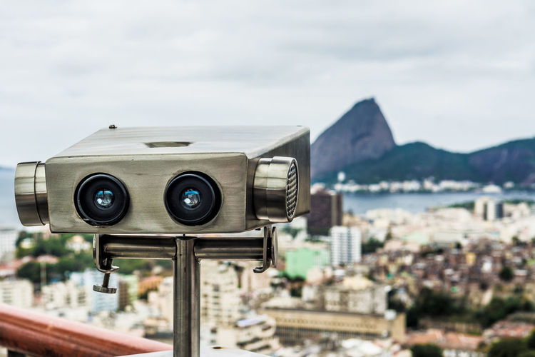 Close-up of binoculars against sky in city