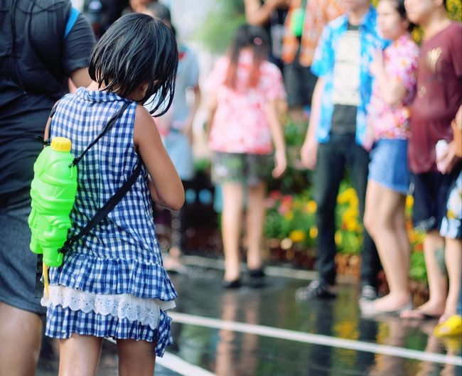Rear view of girl with squirt gun standing on footpath during buddhist new year