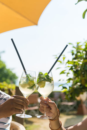 Couple drinking Mojito cocktails in cozy outdoor bar at the beach. Elderly male hand and hand of a young woman are holding the glasses under an umbrella. Cocktail EyeEmNewHere Glasses Lake Constance Alcohol Alcoholic Drink Bodensee Drinking Mojito Two Two People Umbrella Yellow