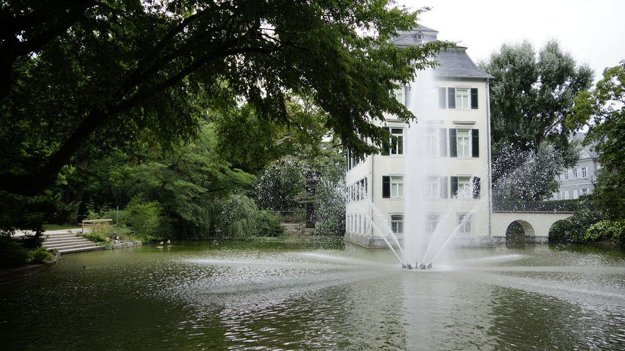 Tree Water Plant Built Structure Architecture Building Exterior Nature Building Growth Waterfront No People Beauty In Nature Day Motion Outdoors Long Exposure Lake House Scenics - Nature Spraying Flowing Water Flowing Power In Nature Popular Places