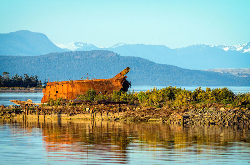 Shipwreck at lakeshore by mountains