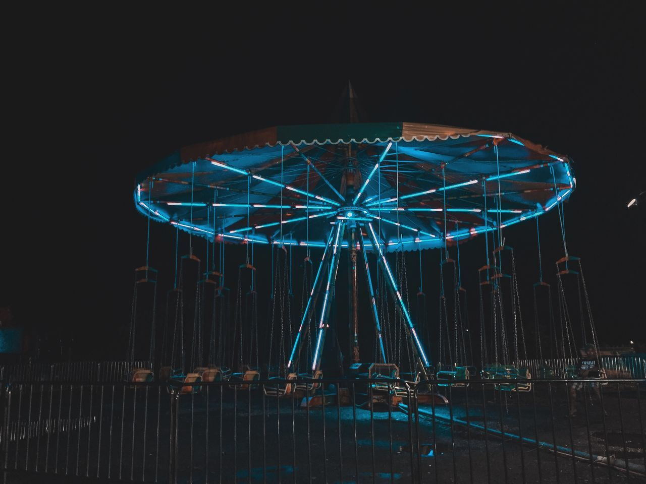 Illuminated carousel against sky at night