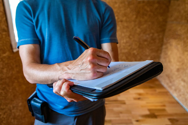 Midsection of man reading book while sitting on table