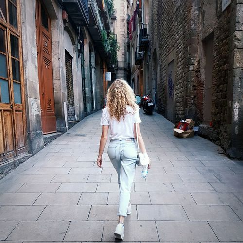 Rear View Of Woman On Footpath Amidst Buildings In City
