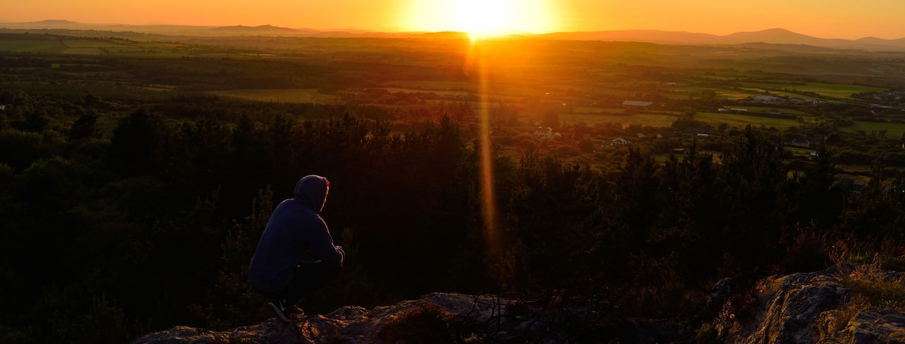 Full length of man crouching on cliff against landscape during sunset