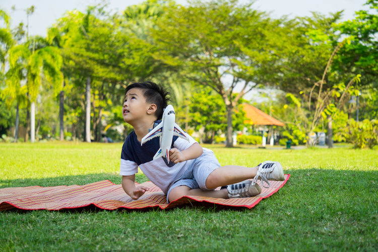 Boys Casual Clothing Child Childhood Day Full Length Grass Happiness Nature One Person Outdoors Park - Man Made Space People Real People Sitting Sky Tree