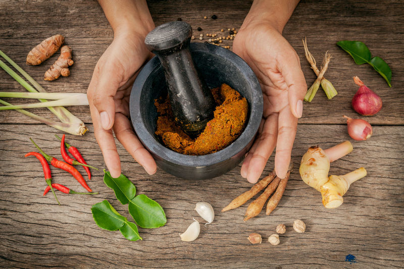 Cropped hands of person mixing spices on table