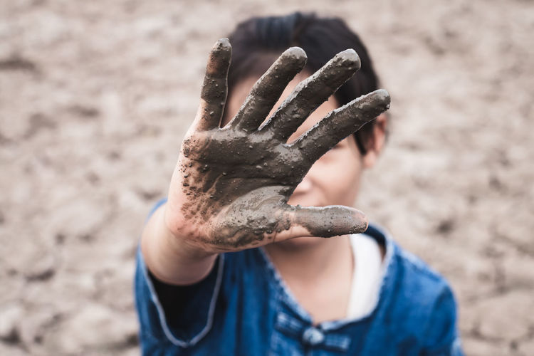 Close-up of girl with muddy hand on drought field