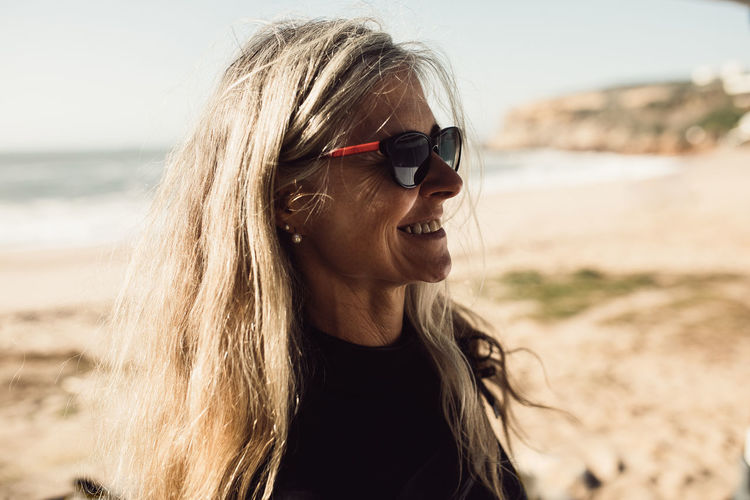 Close-up of smiling woman wearing sunglasses at beach
