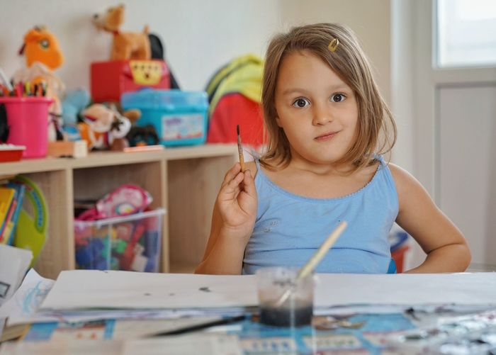 Portrait Of Smiling Girl Holding Paintbrush On Table At Home