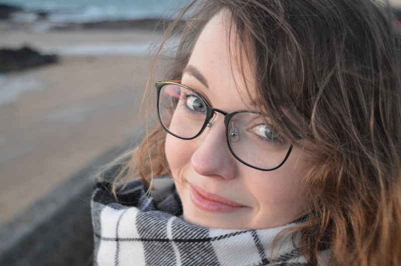 Portrait Of Smiling Young Woman Wearing Eyeglasses At Beach
