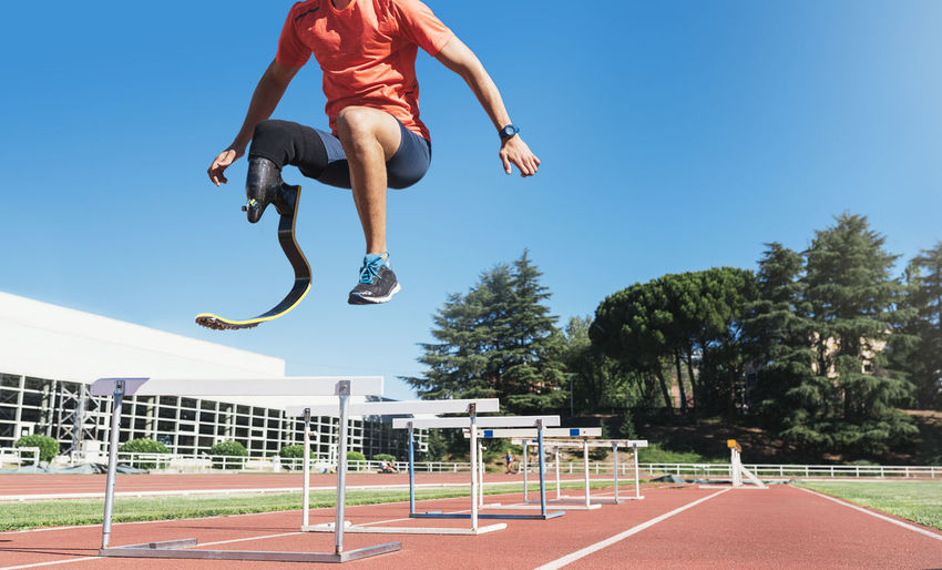 Low section of athlete with prosthetic leg jumping on sports track