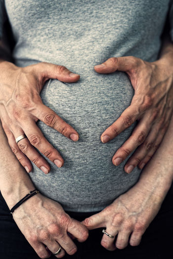 Cropped image of man with hands of pregnant woman belly