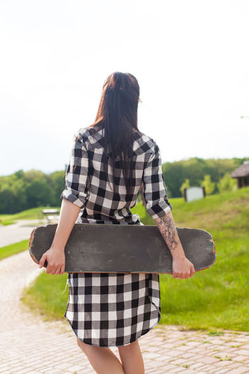 Young woman in long shirt is holding her skate behind on the background of park. Outdoors Hair Hairstyle Striped Rear View Adult Young Adult Standing Young Women Sky Day Women Checked Pattern Three Quarter Length Focus On Foreground Nature Casual Clothing Lifestyles Leisure Activity Real People One Person