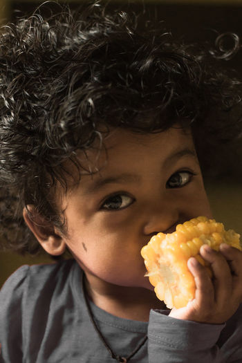 Close-Up Portrait Of Boy Eating Corn