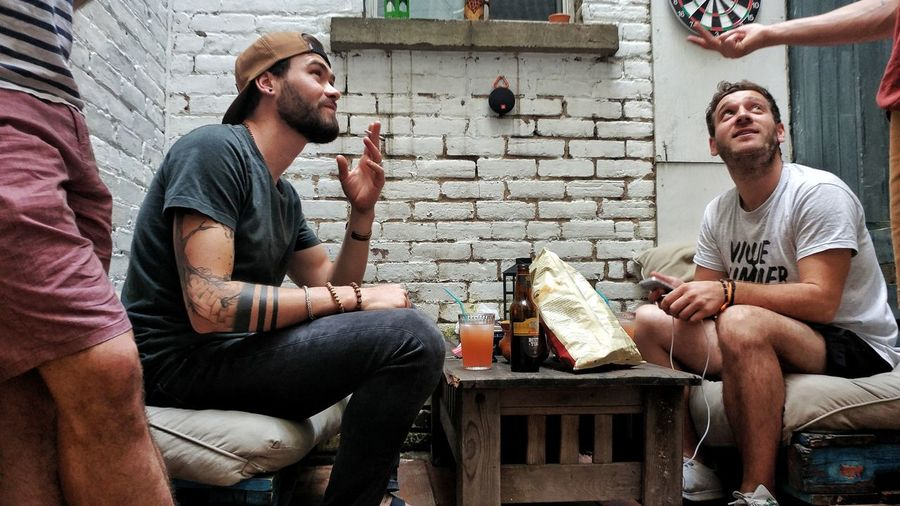 Male Friends Having Drinks On Table At Home