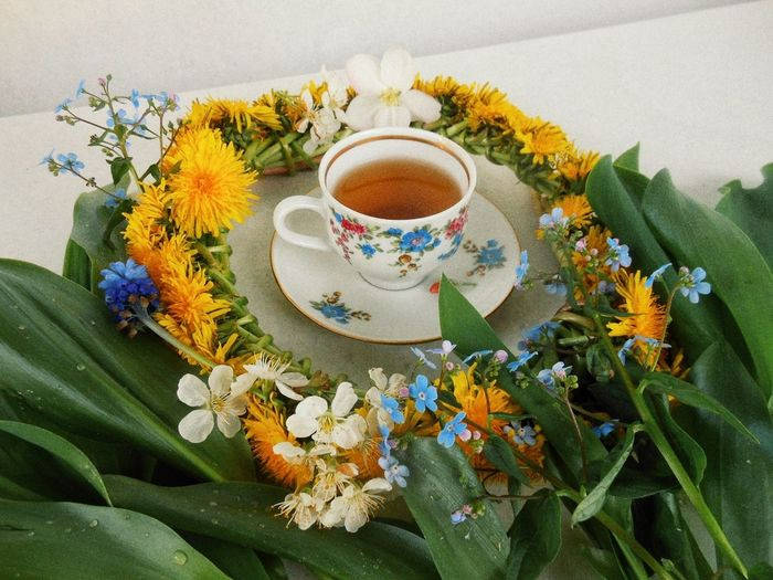 Close-Up Of Tea Amidst Flowers On Table