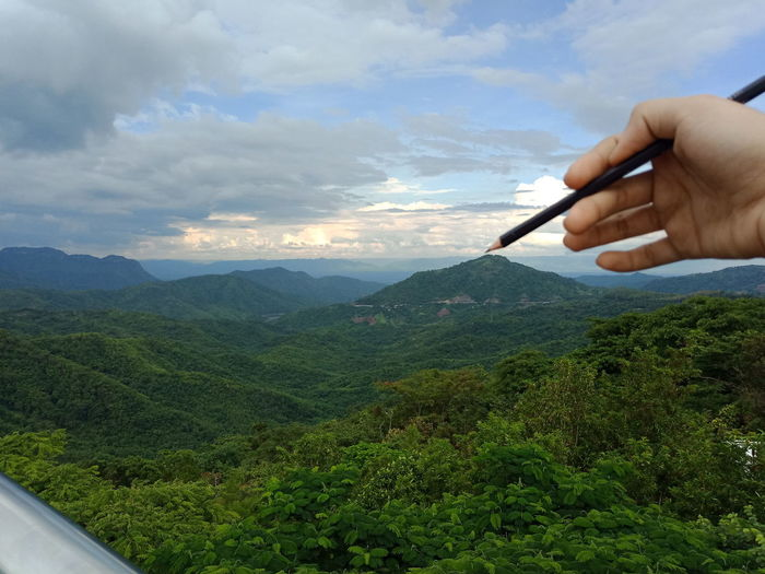 Person holding pencil against mountains