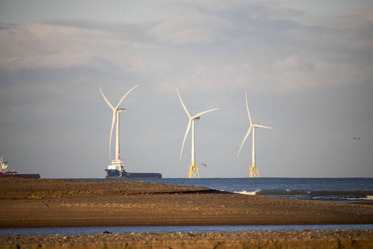 Wind turbines on beach against sky