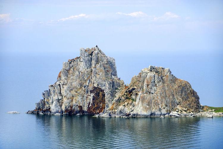 Rocky cliff on sea against sky