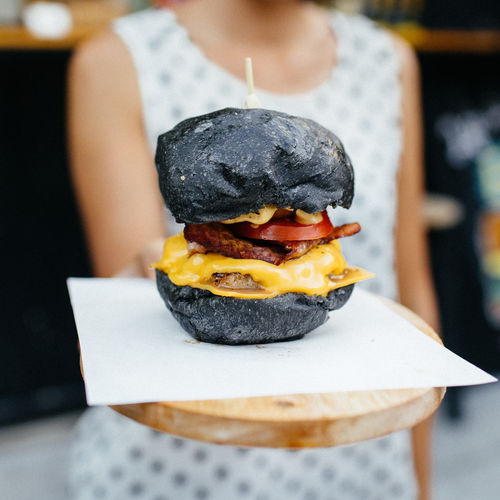 Close-Up Of Burger Held By Woman