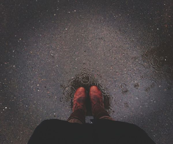 Low section of man wearing shoes standing on wet street