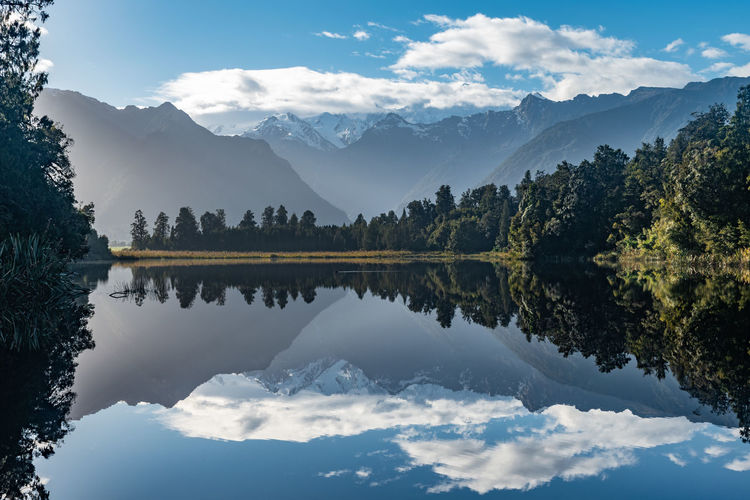 Scenic view of lake and mountains against sky with reflections at lake matheson, new zealand