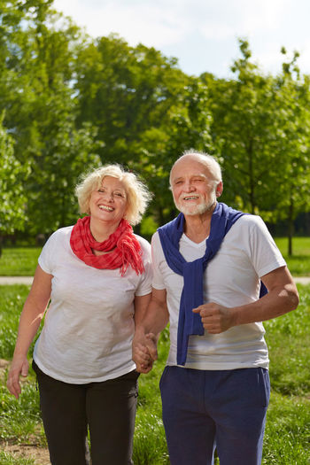 Portrait Of Cheerful Senior Couple Standing At Park