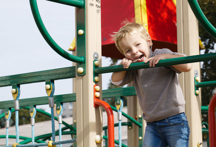 Low angle portrait of smiling boy on slide