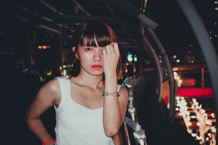 Portrait of young woman standing in footbridge at night