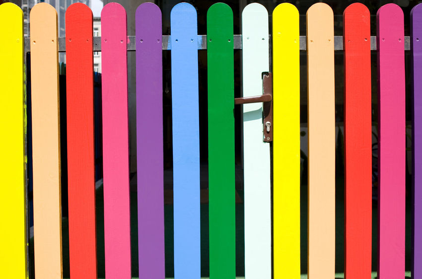 Multicolored rainbow picket fence with brown handle in open air in Warsaw, Poland. Horizontal orientation, nobody, front view detail. Colored Colour Coloured Colours Door Entrance Fence Handle Knob Multi Colored Multicolored Multicoloured No People Rainbow Colors Variation Variety Various Various Colors Yellow