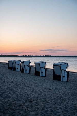 Beach Beauty In Nature Chair Dusk Horizon Horizon Over Water In A Row Land Nature No People Orange Color Outdoors Sand Scenics - Nature Sea Sky Sunset Tranquil Scene Tranquility Water