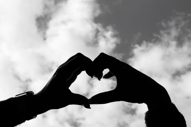 Cropped hands of woman making heart shape against cloudy sky