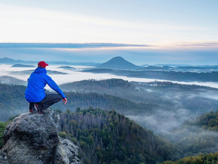 Sitting man on sharp rocky edge, enjoy amazing birds view. misty fall landscape bellow.